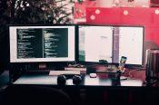 2つのパソコンとスマホなどがある仕事の空間